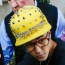 Justin Bieber departs his hotel wearing a yellow studded baseball hat